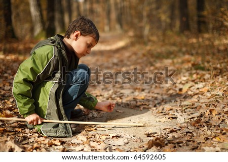 Cute kid writing on the ground with a stick in the forest - stock photo