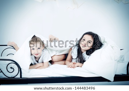 Cute kids lying together on the bed under the blanket. Dream world. - stock photo