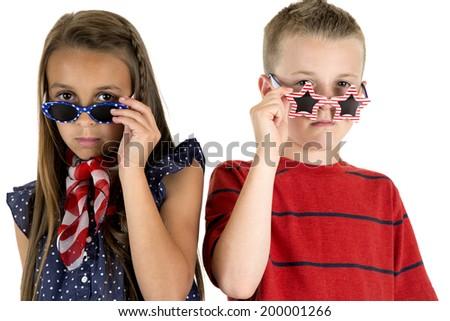 cute kids peering over American patriotic glasses - stock photo