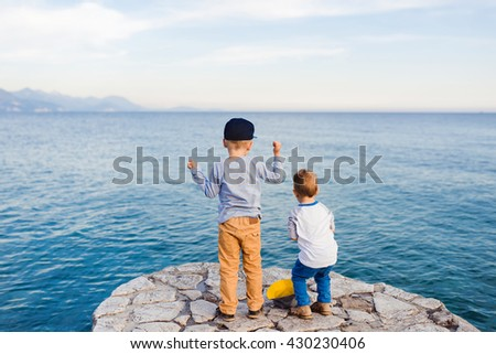 Cute kids playing near ocean, standing on a pier throwing stones. Who throws the farthest - stock photo