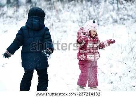 cute kids playing outdoors in winter time, brother and sister - stock photo