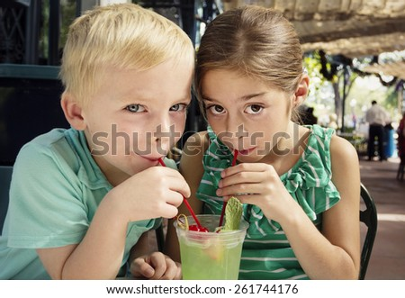 Cute kids sharing a mint julep drink at a cafe - stock photo
