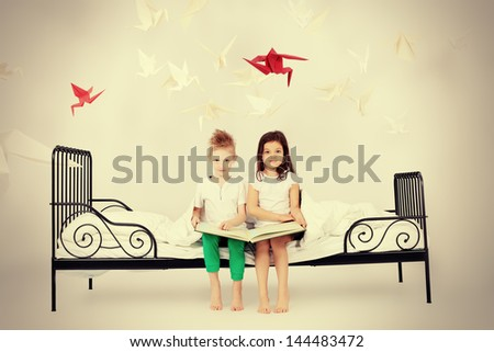 Cute kids sitting together on the bed and reading fairy tales. Dream world. - stock photo