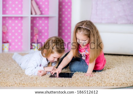 Cute Kids using modern tablet computers laying on the floor in the polka-dot bright pink room at home fun game together - stock photo
