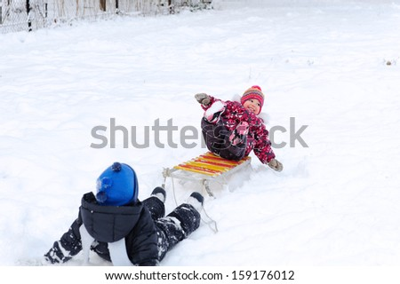 Cute kindergarten boy pulling his young sister on sled - stock photo