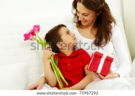 Cute lad with bunch of beautiful tulips looking at his mother with giftbox - stock photo