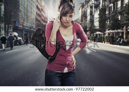 Cute lady speaks by phone on the street - stock photo