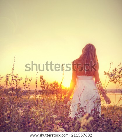 Cute lady walking through the meadow - stock photo