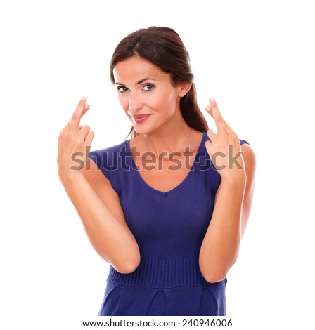 Cute latin woman making a wish and luck sign while looking at you in white background - stock photo