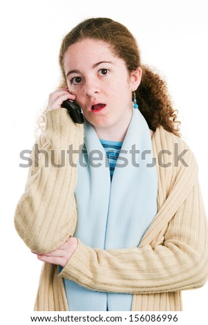 Cute latina tween teenage girl talking on the phone with shocked expression.  Isolated on white.   - stock photo
