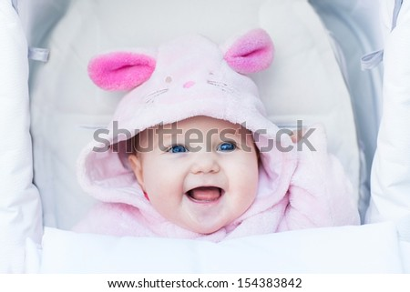 Cute laughing baby girl enjoying a stroller ride on a cold winter day wearing a warm pink bunny snow suit - stock photo