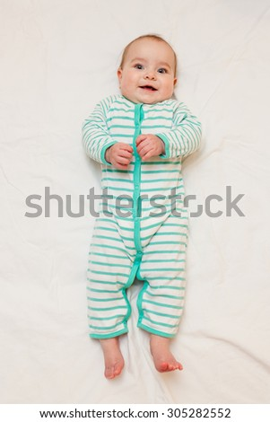 Cute laughing baby  in striped sleep suit lying on his back on white sheet. Baby looking straight at the camera.  - stock photo