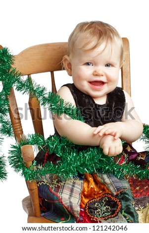 Cute laughing baby in velvet embroidered patchwork dress sits in rocking chair with festive garland. Vertical, isolated/cut out on white background, copy space.