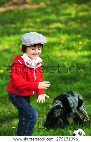 Cute laughing boy and his dog, playing in the park, springtime, daytime - stock photo