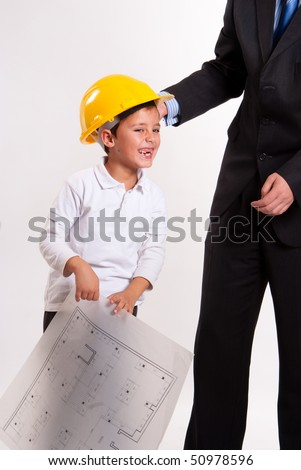 Cute laughing boy with a safety helmet, holding a plan, with his dad - stock photo