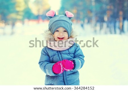 Cute laughing little child on snow walking in winter day - stock photo