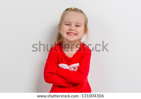 cute laughing little girl in red sweater with her arms folded