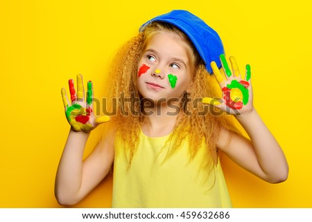 Cute laughing little girl with painted colorful hands over bright yellow background. Happy childhood.  - stock photo
