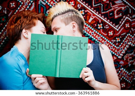 Cute lesbian couple read together lying on the carpet. Selective focus on book - stock photo