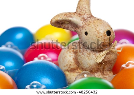 Cute litte Easter bunny sitting between colourful Easter eggs on white background. - stock photo