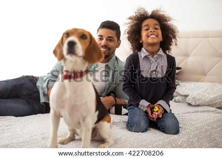 Cute little african american girl playing with her dog.