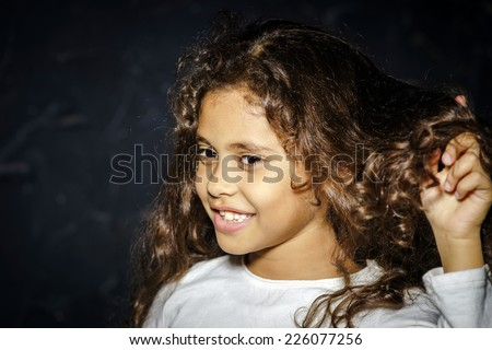 Cute little african-american girl portrait on black background - stock photo