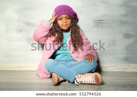 Cute little African American girl sitting against grey wall. Fashion concept
