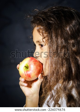 Cute little african-american girl with red apple on black background - stock photo