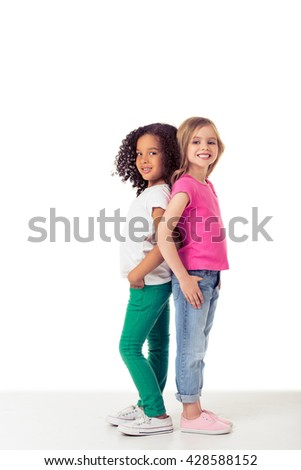 Cute little Afro American and caucasian girls are looking at camera and smiling while standing back to back, isolated on a white background - stock photo
