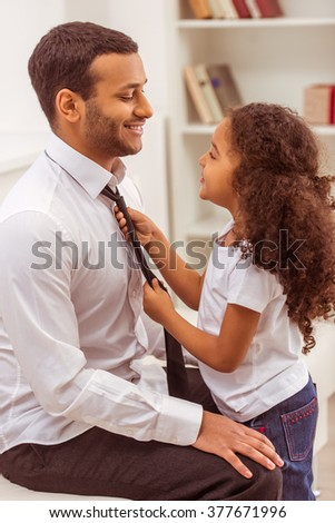 Cute little Afro-American girl adjusting her handsome young father tie. Both looking at each other and smiling. - stock photo