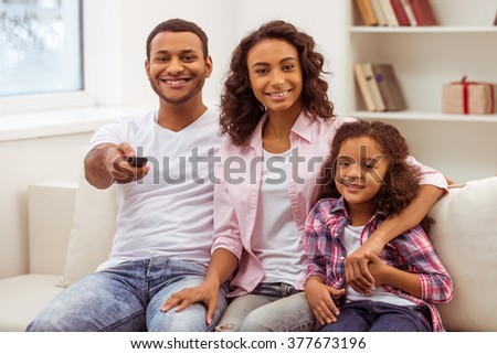 Cute little Afro-American girl and her beautiful young parents hugging, looking at camera and smiling while sitting on a sofa in the room. Father holding a remote control. - stock photo