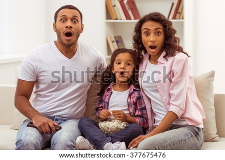 Cute little Afro-American girl and her beautiful young parents looking at camera and showing surprise while sitting on a sofa and watching TV.  - stock photo