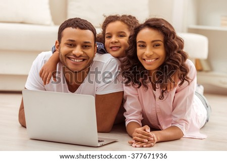 Cute little Afro-American girl and her beautiful young parents using a laptop, looking at camera and smiling while lying on the floor in the room. - stock photo