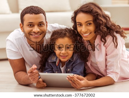 Cute little Afro-American girl and her beautiful young parents using a tablet, looking at camera and smiling while lying on the floor in the room.
