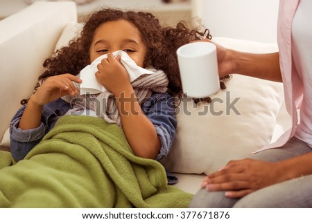 Cute little Afro-American girl with scarf on her neck is ill, lying in bed and blowing her nose. Mother holding a cup.