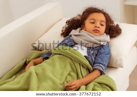 Cute little Afro-American girl with scarf on her neck lying in bed ill - stock photo