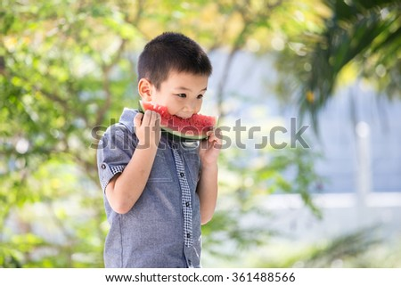 Cute little asian boy eating watermelon in park with sunshine - stock photo