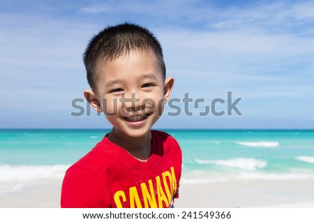 Cute little Asian boy standing on the beach all smiling wearing red Canada shirt - stock photo