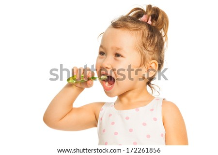 Cute little Asian girl cleaning teeth with toothpaste standing isolated on white with face expression  - stock photo