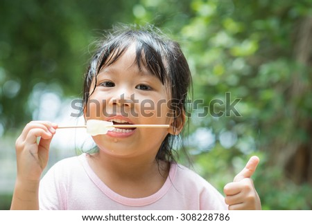 Cute little asian girl like to eating an ice-cream - stock photo