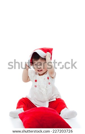 Cute little asian girl   playing happily red santa hat, on white background, shot in studio