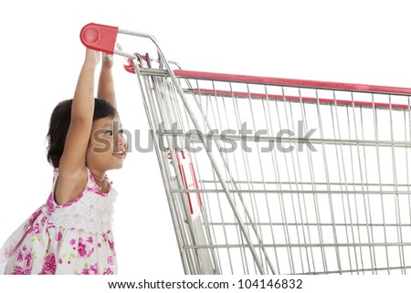 Cute little asian girl pushing trolley shot in studio isolated on white - stock photo