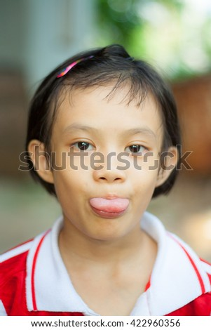 cute little Asian girl showing her tongue. - stock photo