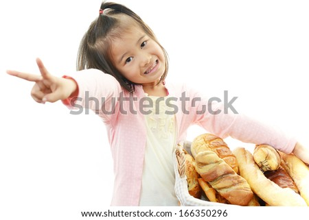 Cute little Asian girl with breads - stock photo