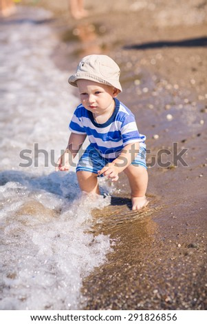 Cute little baby boy exploring the beach at the seaside