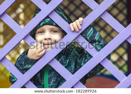 Cute little baby boy  looking through blue fence - stock photo