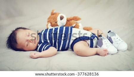 Cute Little Baby Boy Sleeping with Teddy Bear - stock photo