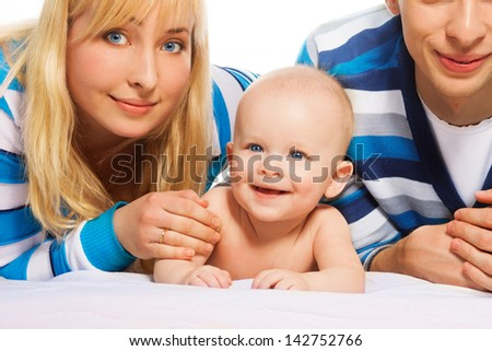 Cute little baby boy smiling happy laying with parents in the bed