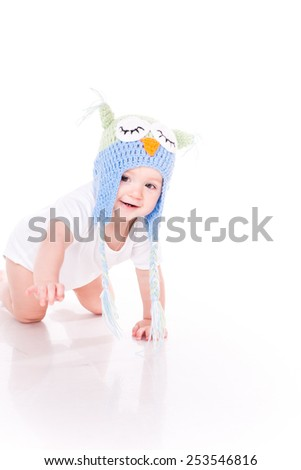 Cute little baby crawling in a owl hat isolated on white