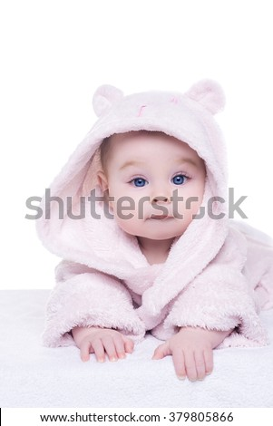 cute little baby girl in pink bathrobe hood lying on her belly. portrait of baby girl on white background. child is looking into the camera. - stock photo